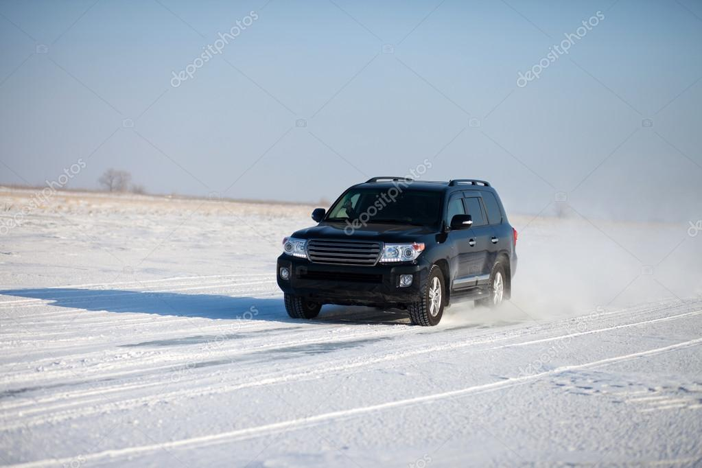 Black car traveling in the snow
