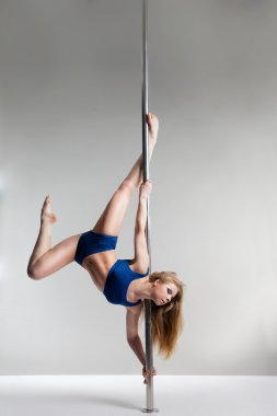 Young slim pole dance woman exercising over white