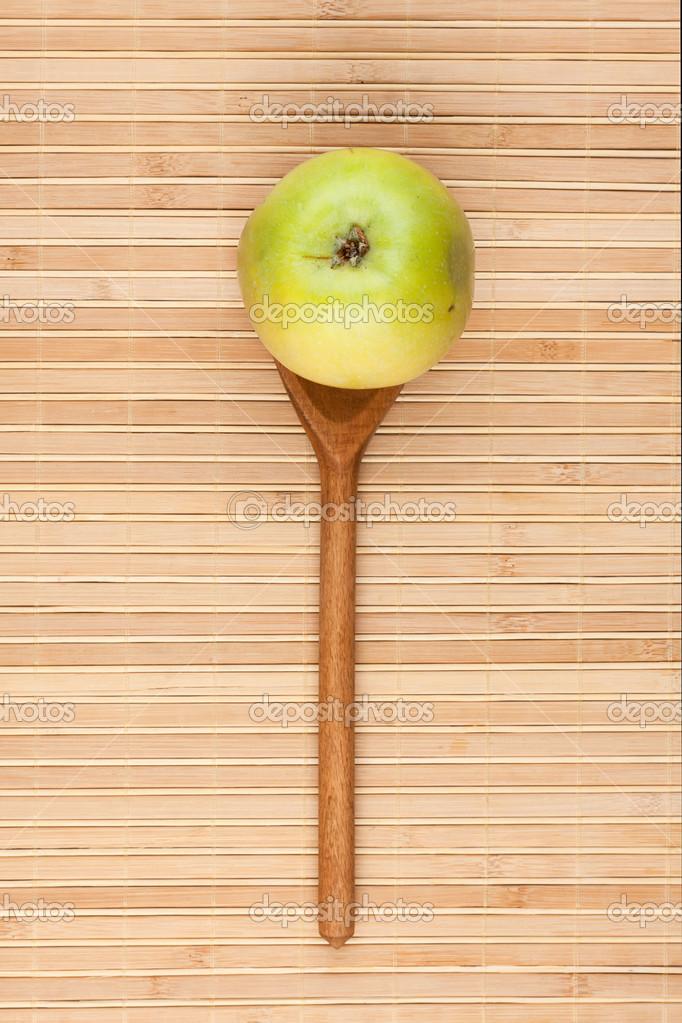 cuchara con manzana verde tumbado en la estera de bambú — Foto de ...