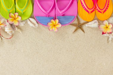 Colorful Flip Flops in the sand with shells and frangipani flowe