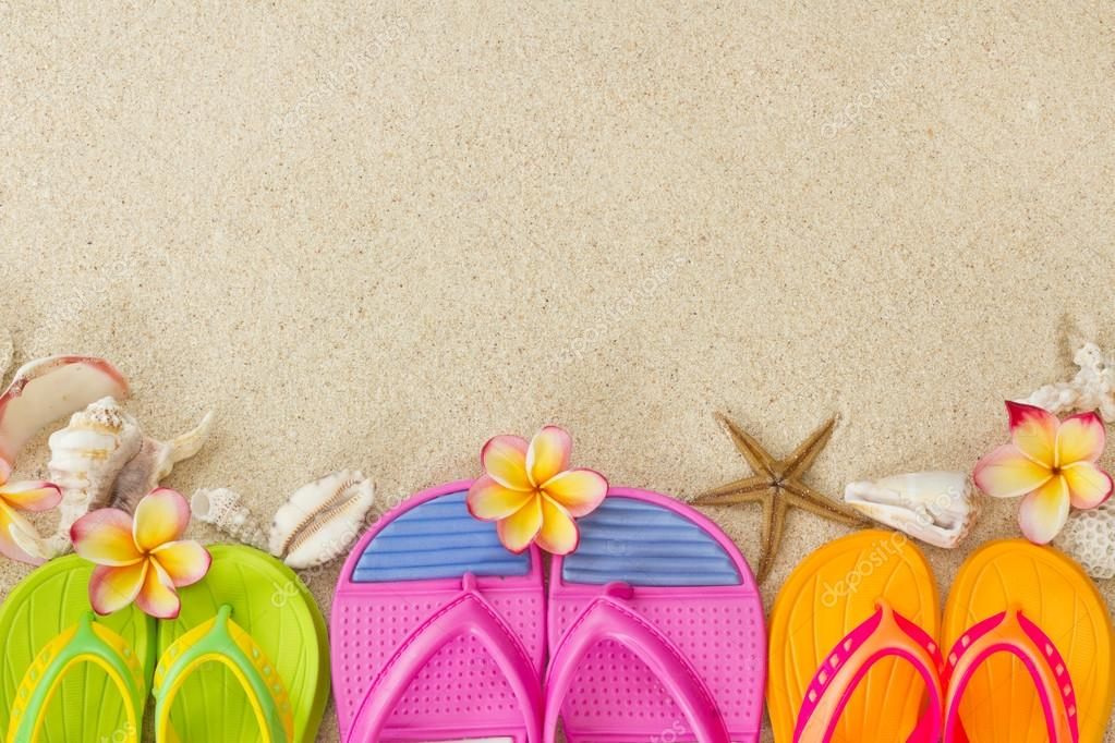 Flip Flops in the sand with shells and frangipani flowers. Summe