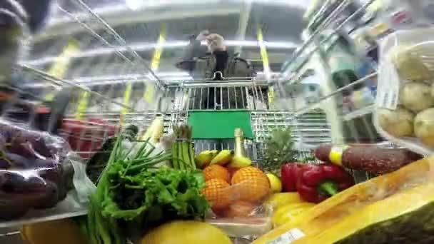az ember egy bevásárló kocsi mozgó gyorsan közötti sorokat egy hatalmas áruház