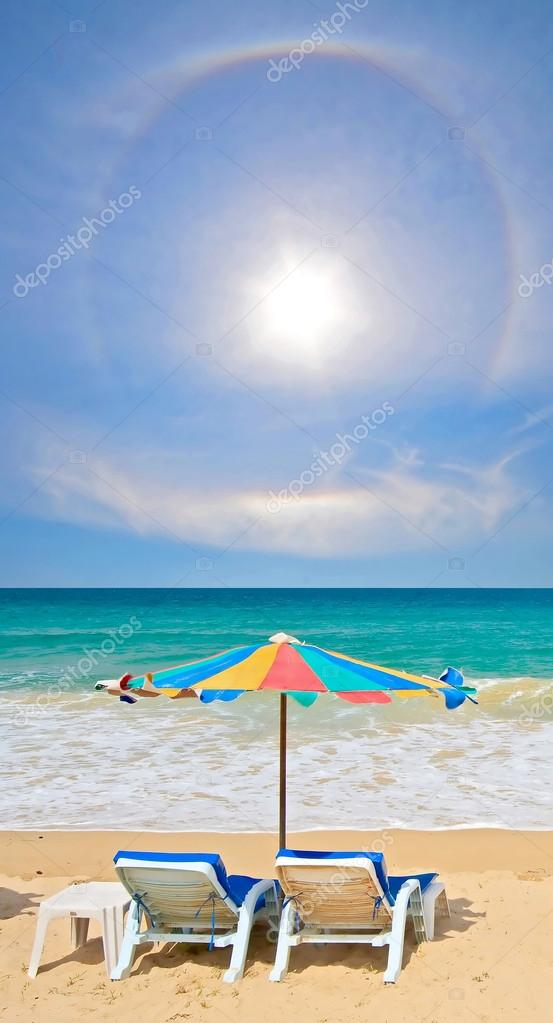 Couple chair and multi-color umbrella on the beach with perfectl