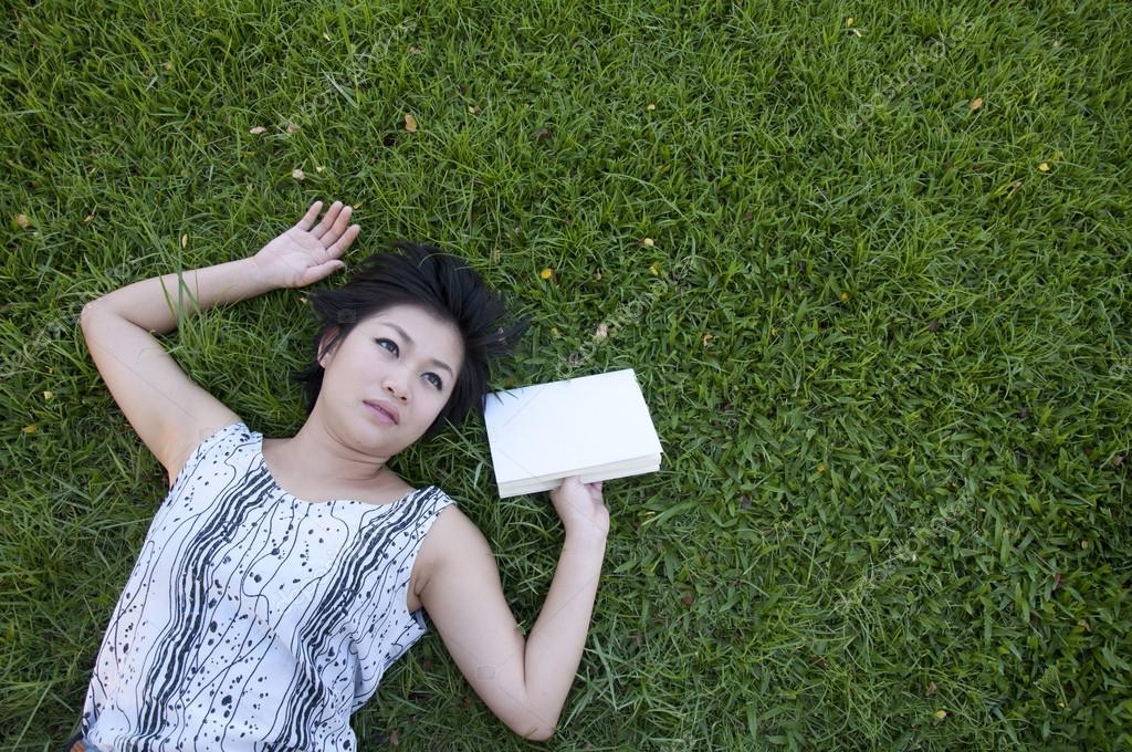 Young woman reading a book in the field
