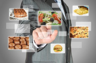 Businessman pushes touch screen button with salad on virtual interface with food