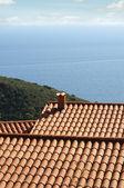 taškovou střechou domu s výhledem na moře