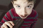 Fotografie lächelnde junge essen Schokolade