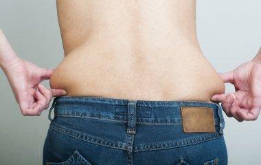 Woman pinching fat from her waist