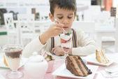 Fotografie Kind isst Erdbeer-Smoothie