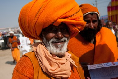 Elderly indian pilgrim in orange turban on the celebration Kumbh Mela