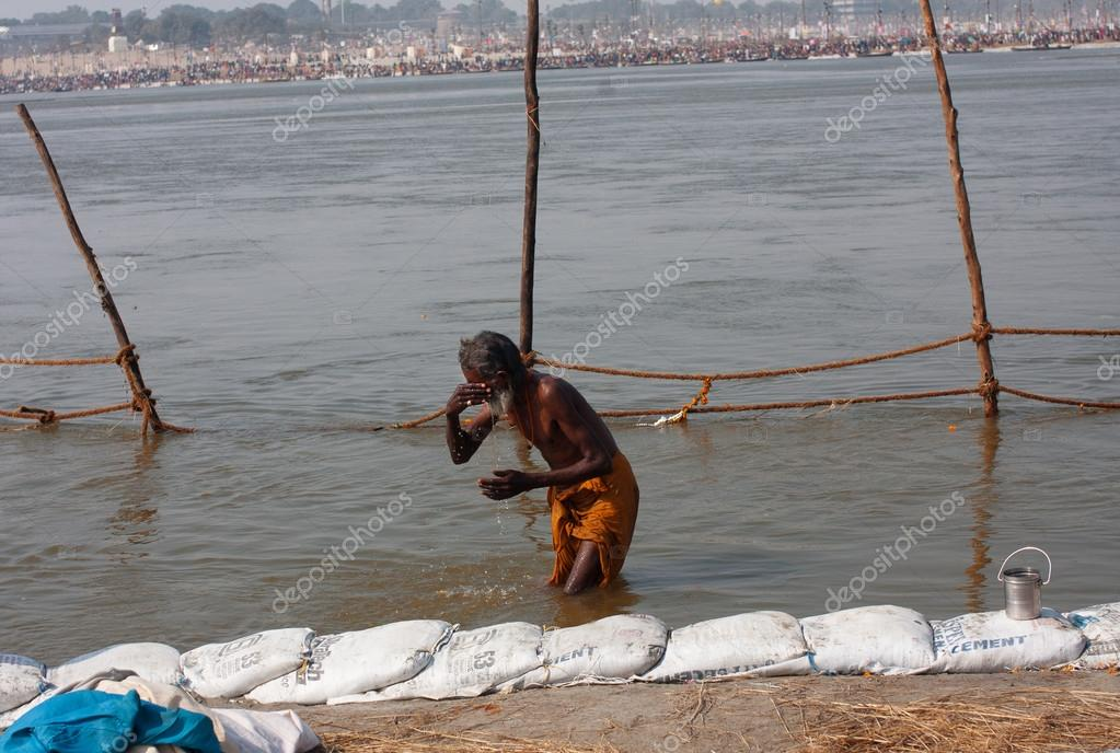 Elderly man bathe in the confluence of the holy Ganges and the Yamuna river