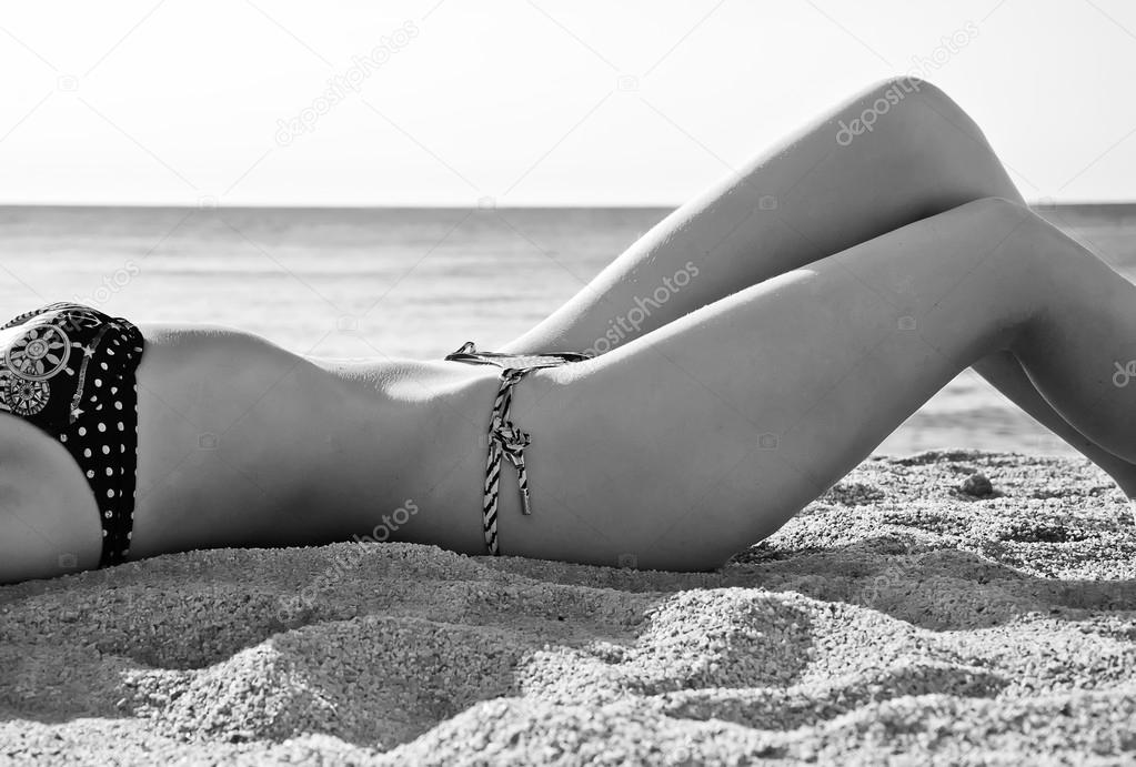 Mid section of young woman body in bikini at beach. Black and white