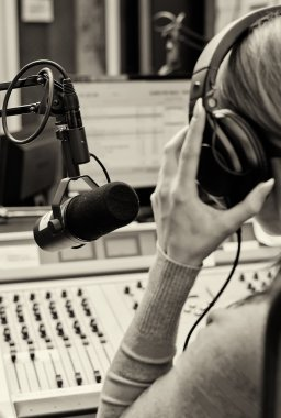Rear view of female dj working in front of a microphone on the radio. Blach