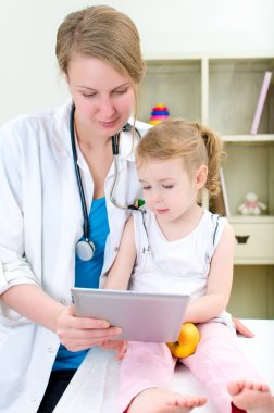 Pediatrician and little girl using tablet computer