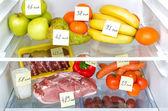 Fotografie otevřené lednice plná ovoce, zeleniny a masa s označené kalorií