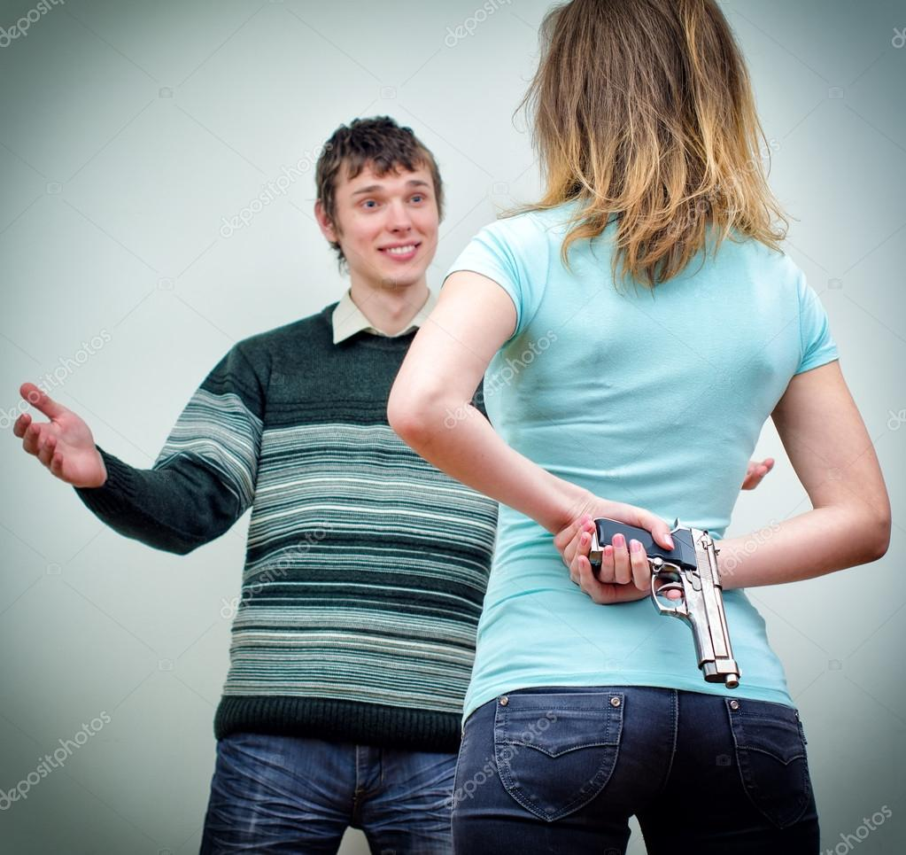 Woman hiding gun underhand talking to man