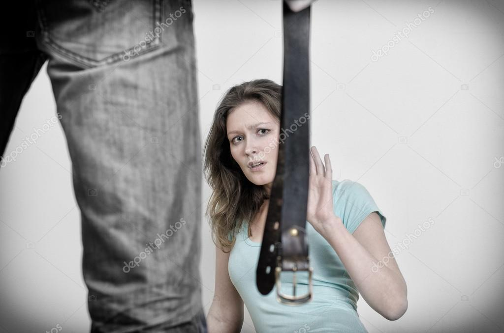 Man with belt coming to his wife. Home violence concept