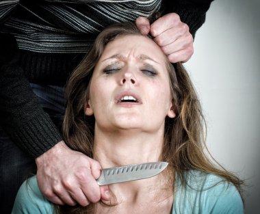 Man holding knife near woman's throat