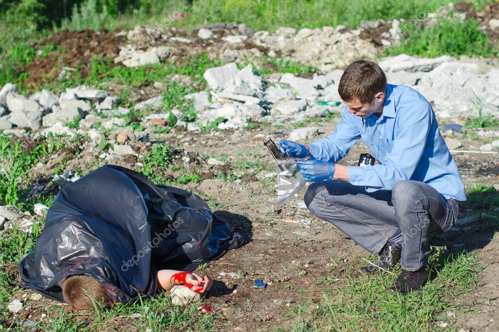 Young male criminalist inspecting crime scene