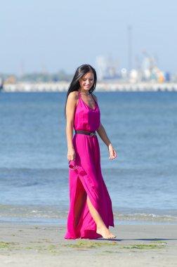 Woman in pink dress walking on the beach