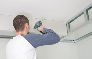 Builder mounting gypsum plasterboard frame on the wall