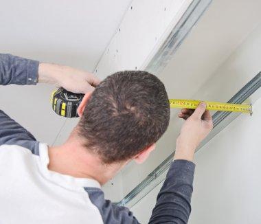 Man measuring gypsum plasterboard frame