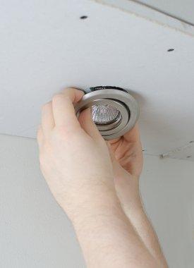 Male hands installing light bulb