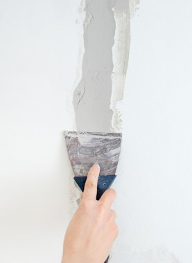 Female hand repairs wall with spackling paste