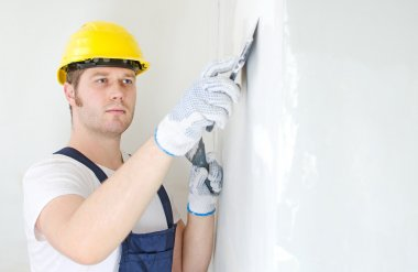 Male builder repairs wall with spackling paste