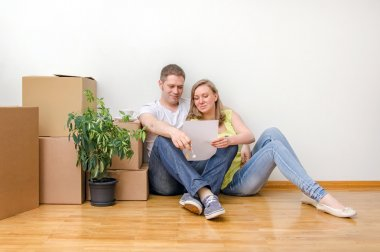 New home concept. Happy family sitting near boxes.