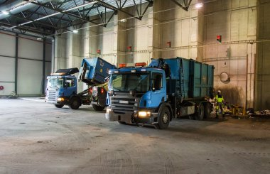 Trucks unloading garbage at recycle plant.