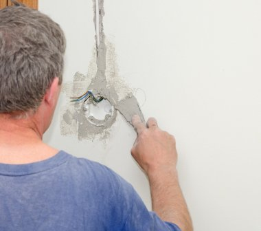 Man repairs wall with spackling paste.
