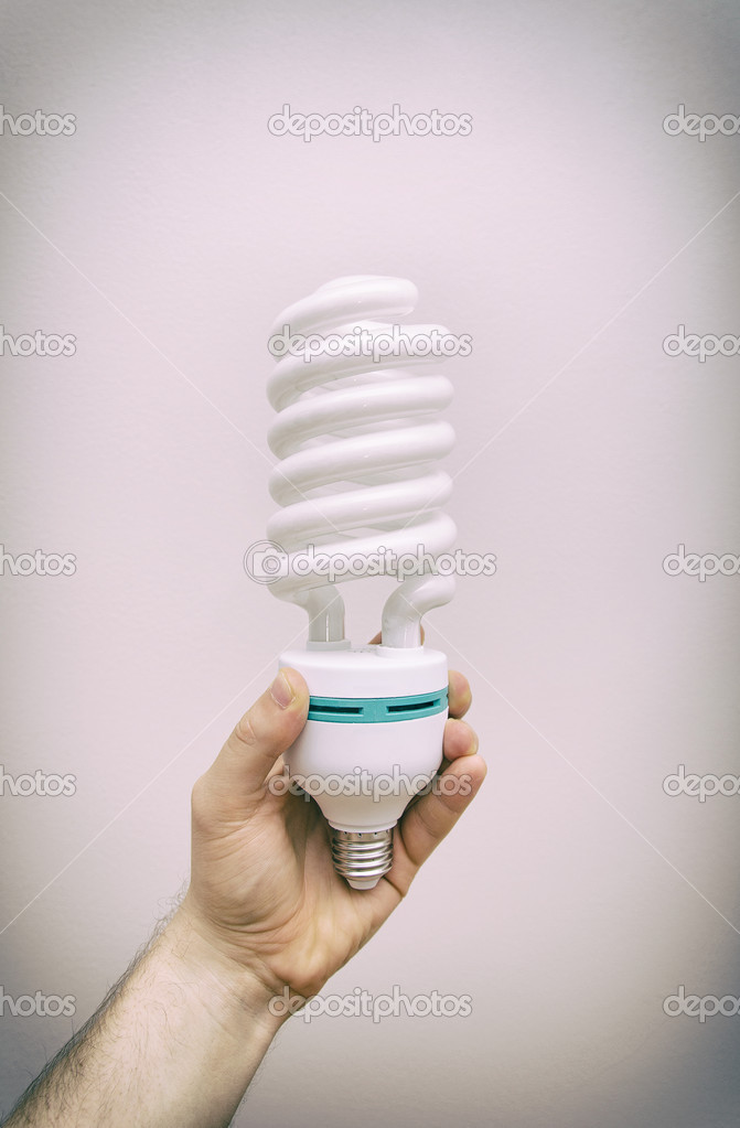 Hand holding big energy efficient spiral-shaped fluorescent lamp ...