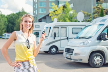 Beautiful young woman offers campervans at shop.