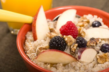 Bowl of steel cut oats served with fresh fruit and honey