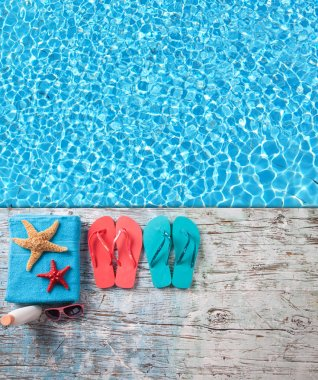Summer accessories on wood with swimming pool surface