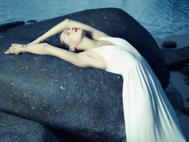 Beautiful elegant lady at huge boulder
