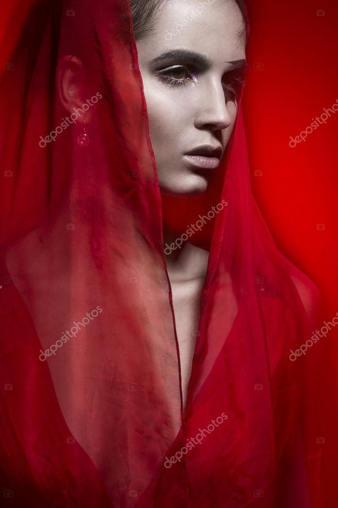 Beautiful hot brunette woman in red dress on red portrait fashion