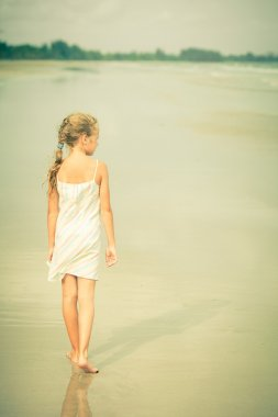 Lonely young girl walking on the beach