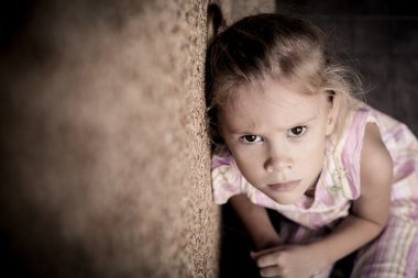 portrait of a sad little girl sitting near the wall