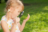 One little girl with magnifying glass outdoors in the day time