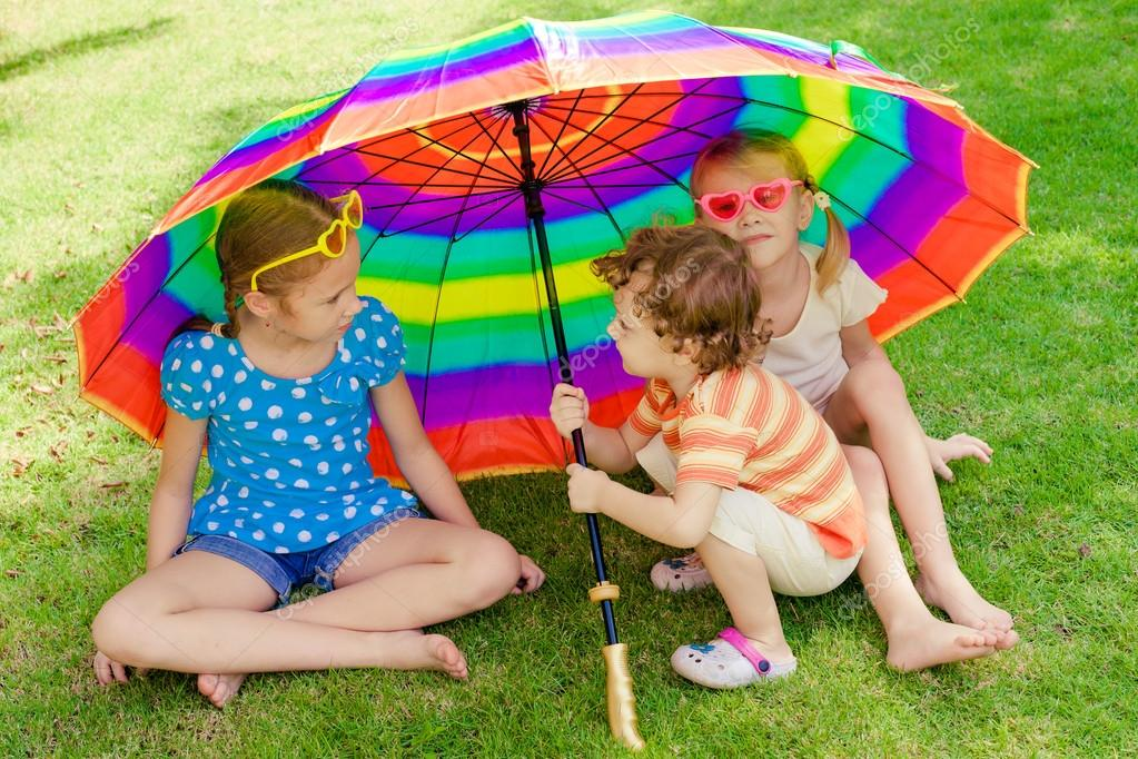 kids playing on the nature with an umbrella