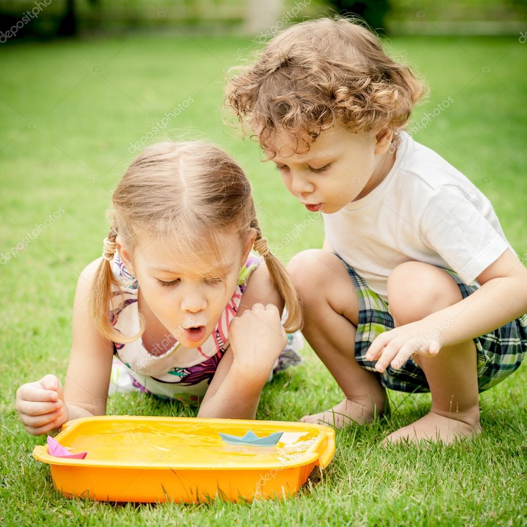 two happy little kids playing in the garden