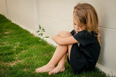 Fotografie Portrait of sad little girl sitting near  wall in the day time