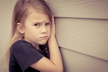 Portrait of sad little girl sitting near  wall in the day time