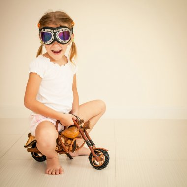 little girl in glasses on toy motorcycle