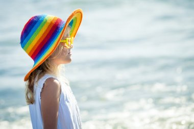 happy little girl in the hat  standing at the beach in the day t