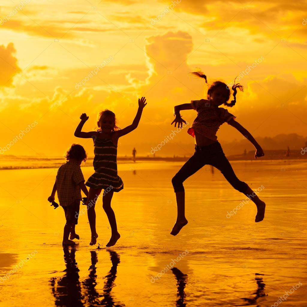 Happy children playing at the beach on the dawn time