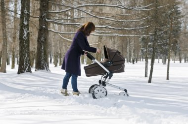 Woman walking with baby carriage
