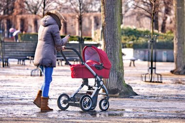 Young woman walking with her baby in the park
